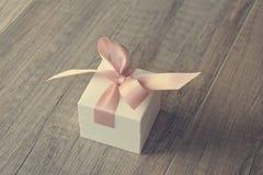 在白色箱子的一件礼物有一把桃红色弓的 免版税库存图片