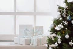 在白色箱子的圣诞节礼物在一个窗口在圣诞树下 免版税库存照片