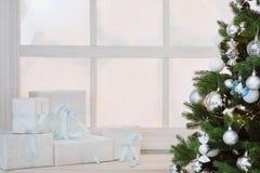 在白色箱子的圣诞节礼物在一个窗口在圣诞树下 免版税库存图片