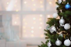 在白色箱子的圣诞节礼物在一个窗口在圣诞树下 图库摄影