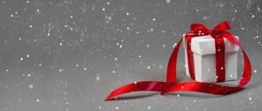 在白色箱子的圣诞节礼物有在深灰背景的红色丝带的 新年假日构成横幅 复制您的文本的空间 免版税库存图片