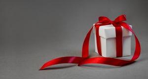 在白色箱子的圣诞节礼物有在深灰背景的红色丝带的 新年假日构成横幅 复制您的文本的空间 库存图片