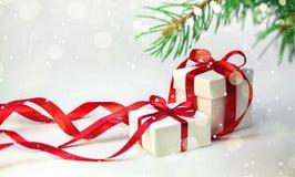 在白色箱子的圣诞节礼物有在轻的背景的红色丝带的与杉树 新年假日构成 复制空间 免版税库存图片