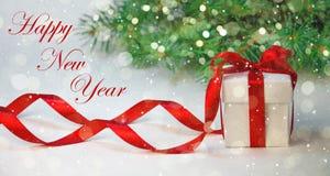 在白色箱子的圣诞节礼物有在轻的背景的红色丝带的与杉树 新年假日构成 免版税库存照片