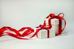 在白色箱子的圣诞节礼物有在轻的背景的红色丝带的 新年假日构成 复制空间 图库摄影