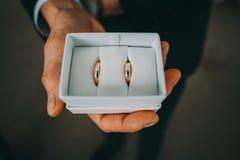 在白色箱子的婚戒在新郎的手上 免版税库存照片