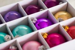 在白色箱子的许多美丽的五颜六色的圣诞节球 图库摄影