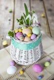 在白色篮子的复活节彩蛋在土气木背景 免版税图库摄影