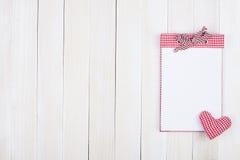 在白色篱芭的红色格子花呢披肩笔记本 免版税库存照片
