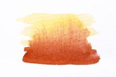 在白色粗砺的纹理纸的橙色水彩刷子冲程 免版税库存照片