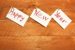 在白色纸片的题字新年好 背景木头颜色 免版税库存照片