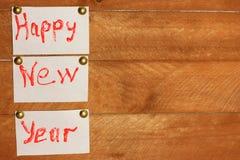 在白色纸片的题字新年好 自然背景的木头 库存照片