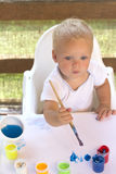 在白色纸的周道的男婴图画与油漆的 免版税库存图片
