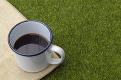 在白色罐子杯子的咖啡在草背景 免版税库存照片