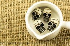 在白色罐,大袋背景里面的微型头骨 库存图片