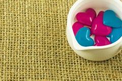 在白色罐,大袋背景里面的桃红色和蓝色心脏 图库摄影