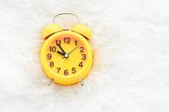 在白色羊毛的黄色闹钟 晚和懒惰时间概念 Mo 免版税库存图片