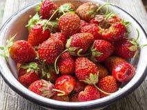 在白色老盘的成熟红色草莓在木桌上 免版税库存照片