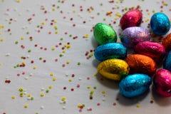 在白色背景和五颜六色的五彩纸屑的许多常设色的巧克力复活节彩蛋 免版税库存图片