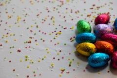 在白色背景和五颜六色的五彩纸屑的许多常设色的巧克力复活节彩蛋 免版税库存照片