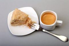 在白色背景和传统浓咖啡咖啡的自创拿破仑吹蛋糕隔绝的板材 特写镜头 库存照片