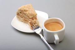 在白色背景和传统浓咖啡咖啡的自创拿破仑吹蛋糕隔绝的板材 特写镜头 图库摄影