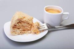 在白色背景和传统浓咖啡咖啡的自创拿破仑吹蛋糕隔绝的板材 特写镜头 库存图片