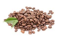 在白色背景和叶子隔绝的咖啡粒 免版税库存照片