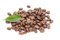 在白色背景和叶子隔绝的咖啡粒 库存图片
