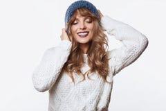 在白色背景和帽子的微笑的白肤金发的妇女隔绝的毛线衣 免版税库存图片