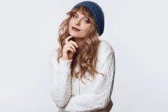 在白色背景和帽子的正面白肤金发的妇女隔绝的毛线衣 免版税库存照片