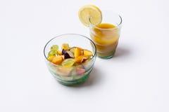 在白色背景和橙汁隔绝的水果沙拉。 免版税库存照片