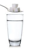 在白色背景和糖隔绝的杯水 免版税库存照片