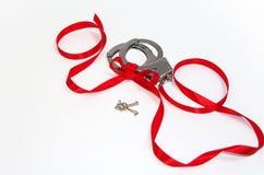 在白色背景和红色丝带隔绝的金属手铐 库存照片