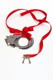 在白色背景和红色丝带隔绝的金属手铐 库存图片