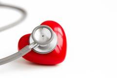 在白色背景和红色心脏隔绝的听诊器 图库摄影