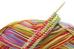 在白色背景和编织针隔绝的编织的五颜六色的混合物彩虹棉花球 舒适编织克洛起点  库存照片