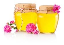 在白色背景和花的蜂蜜隔绝的两朵玻璃瓶子 免版税库存图片