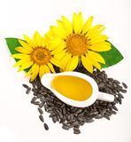 在白色背景和花隔绝的向日葵油、种子 顶视图 库存图片