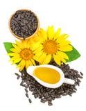 在白色背景和花隔绝的向日葵油、种子 顶视图 免版税库存照片
