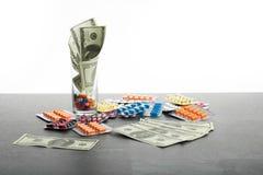在白色背景和药物隔绝的金钱 五颜六色的片剂,胶囊,在美元旁边的药片堆的特写镜头  图库摄影
