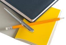 在白色背景和铅笔隔绝的笔记本、笔 r 办公室辅助部件 库存图片