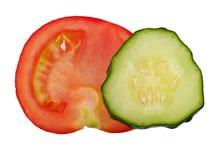 在白色背景和黄瓜隔绝的一部分的蕃茄,顶视图 图库摄影