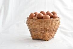 在白色背景填装的篮子的鸡蛋 免版税库存图片