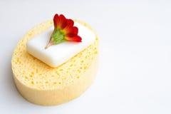 在白色背景安置的一块黄色海绵的使用的肥皂 免版税库存图片
