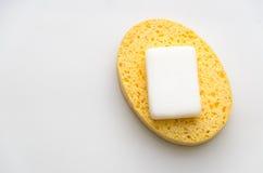 在白色背景安置的一块黄色海绵的使用的肥皂 免版税库存照片