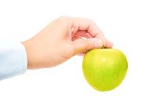 在白色背景对负用手隔绝的绿色苹果 库存照片