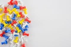 在白色背景左侧,上色推挤别针红色,黄色,白色和蓝色小组 库存照片