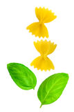 在白色背景或短的面团和牛至叶子隔绝的Farfalle 免版税库存图片