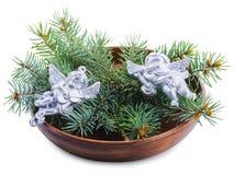 在白色背景有绿色云杉的分支和圣诞节天使的板材隔绝的 库存图片
